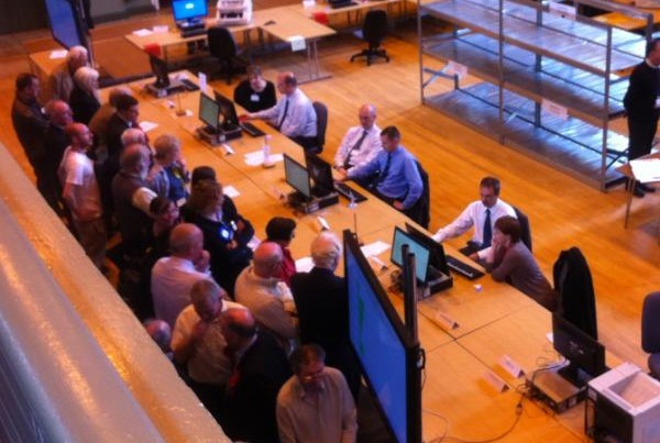 Count staff feed ballots into the computer, while candidates and agents oversee the process